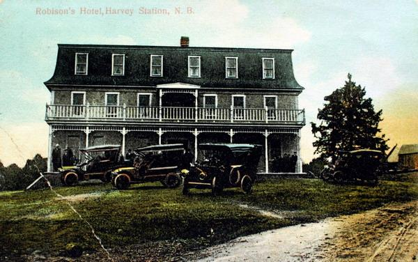 A postcard of 'Robison's Hotel, Harvey Station, N.B.' with guests seated on the veranda and several early automobiles parked on the lawn out front iy was photographed around 1910. Image courtesy of J. Hall.