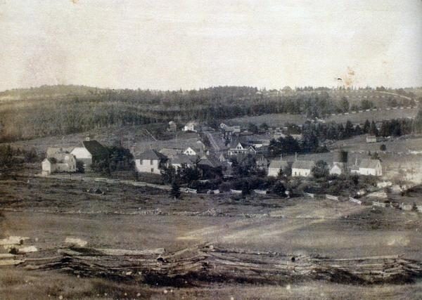 Postcard of village of Harvey Station taken from northwest. Steeple of St. James Presbyterian Church is not present so image was taken brfore 1897 the year the church was completed. Cedar rail 'snake fences' a very typical fencing style in the Harvey area in foreground. Image thanks to J. Hall.