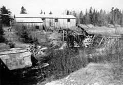 Photograph of Adam's Lumber Mill in York Mills, taken in the 1950's. Image shows dammed head pond and piled logs waiting to be sawed. Mill remained unchanged into the 1970s. Image thanks to J. Hall.
