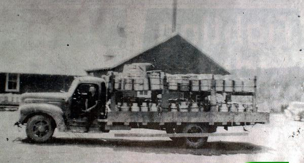 Photograph of Harvey Creamery in June, 1941. The truck driven by George Tracy was loaded with 310 cans of cream which had been picked up between Lower Queensbury by Pokiok and Long's Creek. Photograph in collection of George Tracey. Image courtesy of J. Hall.